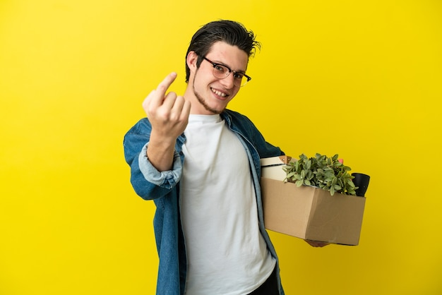 Russian man making a move while picking up a box full of things isolated on yellow background doing coming gesture