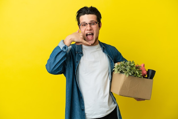 Russian man making a move while picking up a box full of things isolated on yellow background making phone gesture. call me back sign