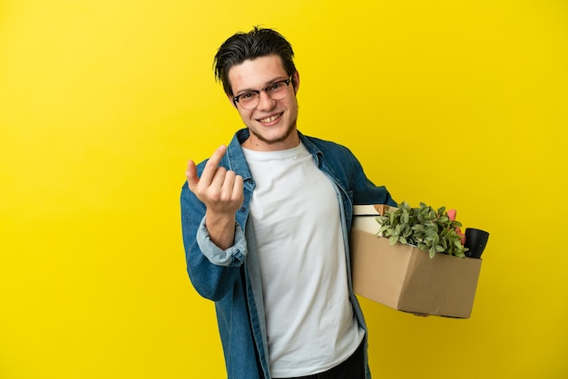 Russian man making a move while picking up a box full of things isolated on yellow surface inviting to come with hand. happy that you came