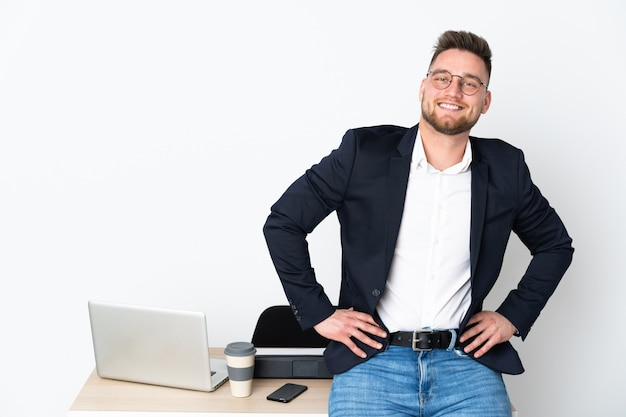 Russian man in an office on white wall posing with arms at hip and smiling