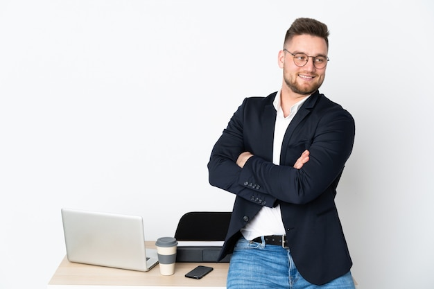 Russian man in a office on white wall with arms crossed and happy