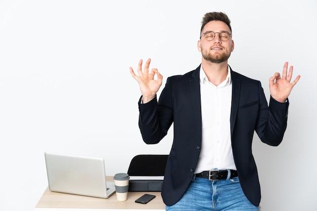 Russian man in a office on white wall in zen pose