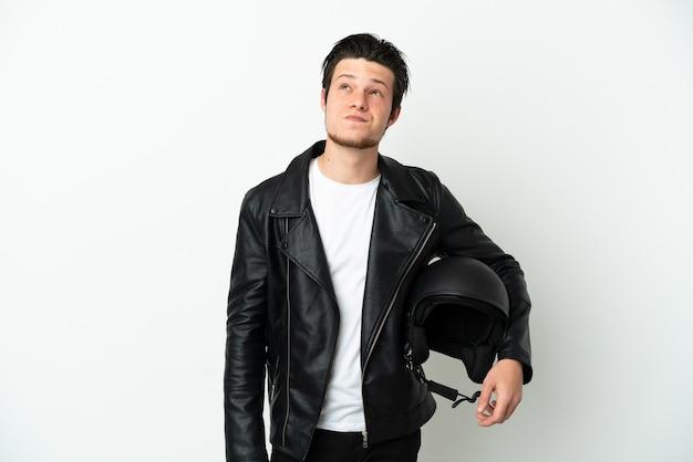 흰색 배경에 고립 찾고 오토바이 헬멧을 가진 러시아 남자