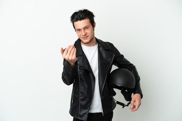 흰색 배경에 격리된 오토바이 헬멧을 쓴 러시아 남자가 손을 잡고 초대합니다. 당신이 와서 행복
