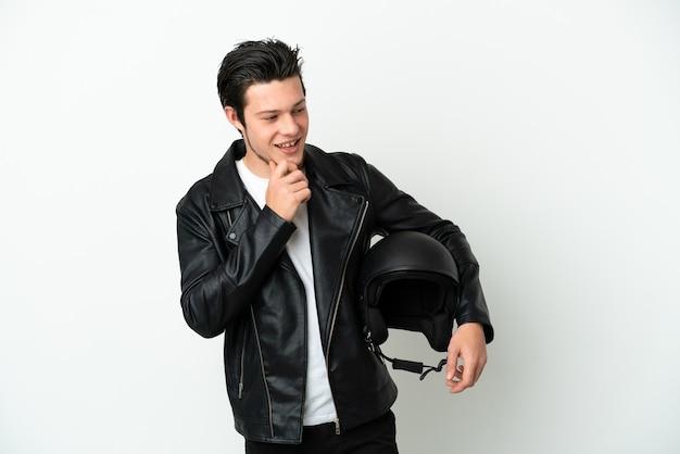 측면을 찾고 웃 고 흰색 배경에 고립 된 오토바이 헬멧을 가진 러시아 남자