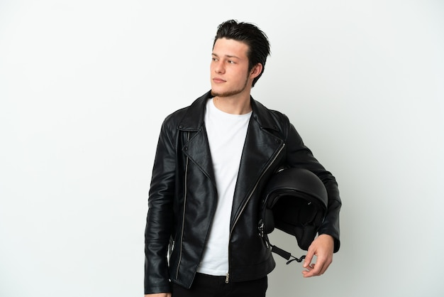 측면을 찾고 흰색 배경에 고립 된 오토바이 헬멧을 가진 러시아 남자
