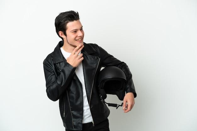 웃는 동안 찾고 흰색 배경에 고립 된 오토바이 헬멧을 가진 러시아 남자