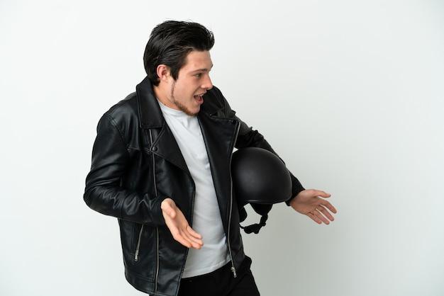 측면을 보면서 놀란 표정으로 흰색 배경에 고립 된 오토바이 헬멧을 쓴 러시아 남자