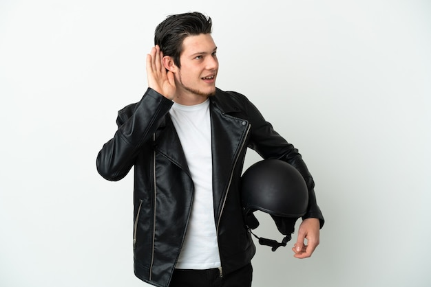 Russian man with a motorcycle helmet isolated on white background listening to something by putting hand on the ear