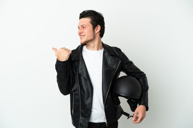 Russian man with a motorcycle helmet isolated on white background pointing to the side to present a product