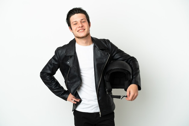 Russian man with a motorcycle helmet isolated on white background posing with arms at hip and smiling