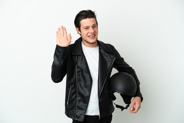 Russian man with a motorcycle helmet isolated on white background saluting with hand with happy expression