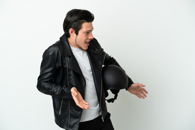 Russian man with a motorcycle helmet isolated on white background with surprise expression while looking side