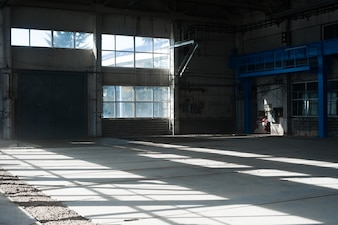 Russian manufacturing factory. Empty hangar building. Blue toned background