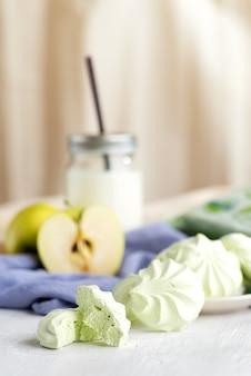 皿にロシアのマシュマロ、テーブルにリンゴとお茶。静物、選択的な焦点。垂直
