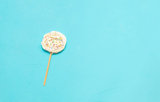 Russian marshmallow zefir on a stick on light blue background. top view with copy space.