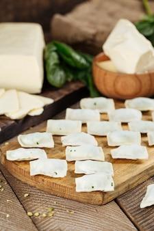 ロシアの郷土料理餃子とチーズとほうれん草。木製の暗いテーブルに小麦粉を黒板に