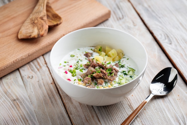 木製のテーブルに牛肉と野菜を添えたロシアのオクローシカの冷たいスープ