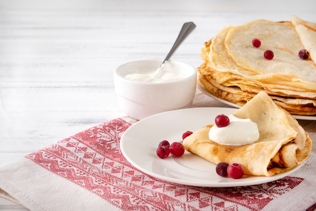 Russian pancakes with berries and sour cream on a plate, on a towel with a red pattern on a white surface,