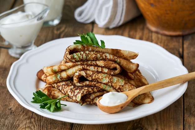 Russian pancakes with fresh parsley and sour cream on a plate