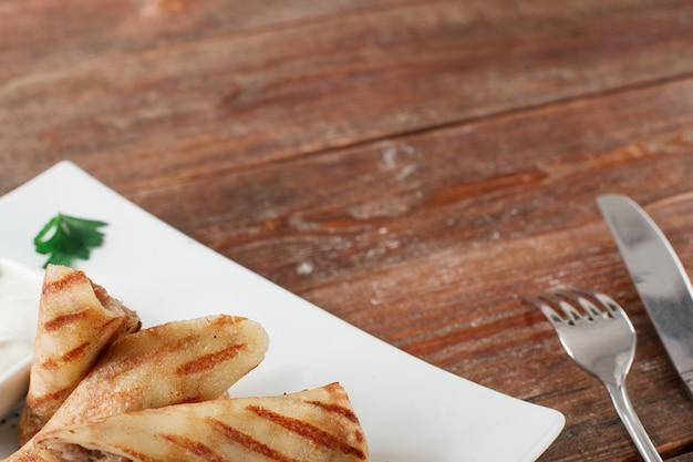 나무 테이블에 고기와 러시아 팬케이크입니다. 흰색 접시에 쇠고기 크레페로 채워진 수 제 음식 배경 롤.