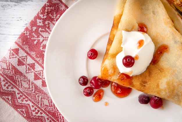 Russian pancakes with sour cream, berries, cranberries and jam on a plate, tea, jam on a towel with a red pattern on a white surface, top view,