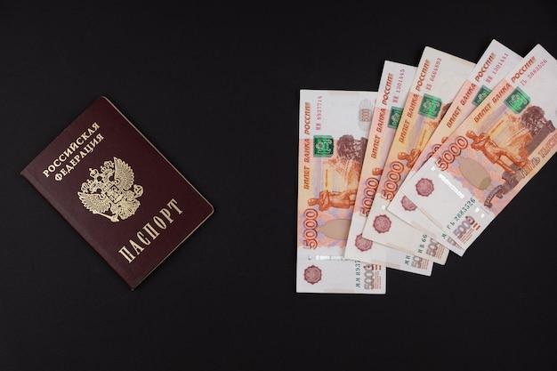 Российский паспорт и российская валюта крупным планом, лежащая на черном фоне