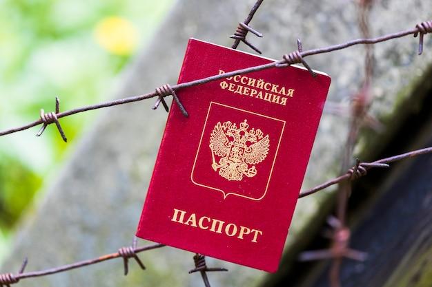 ロシアのパスポートは有刺鉄線に掛かっています。高品質の写真
