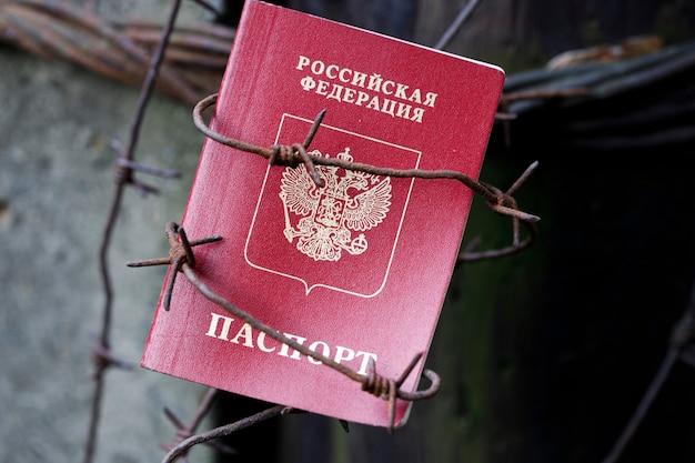 철조망에 묶인 러시아 여권이 기둥에 걸려 있습니다. 고품질 사진