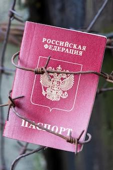 有刺鉄線のロシアのパスポートがポールに掛かっています。高品質の写真