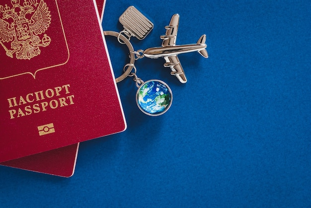 Russian passport for international travel, airplane, globe and luggage models on blue background with copy space
