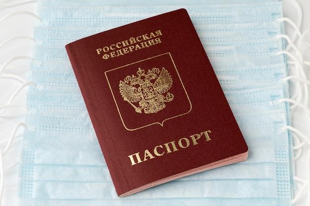 Российский паспорт на фоне защитных антивирусных масок. концепция борьбы с мировой пандемией, страхование от коронавируса, заболеваний, передающихся воздушным путем, гриппа, атипичной пневмонии. текст титульного документа на русском языке.