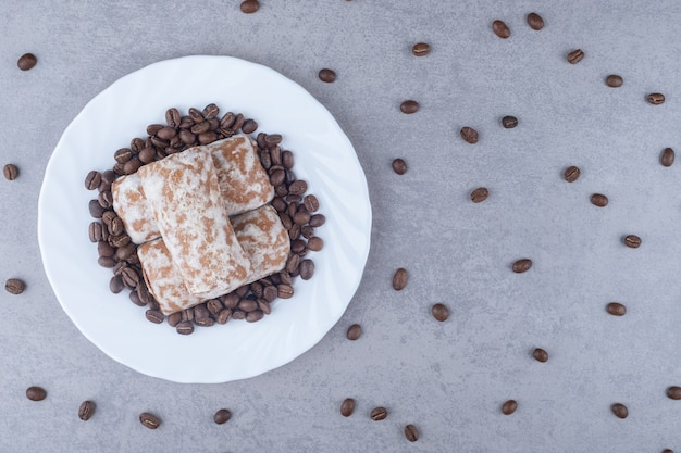 Russian pryanik cookies and coffee beans on a platter on marble