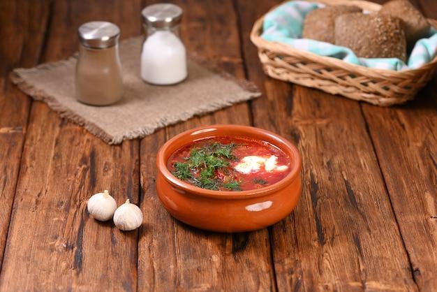 Русский красный борщ со сметаной и укропом в глиняной тарелке