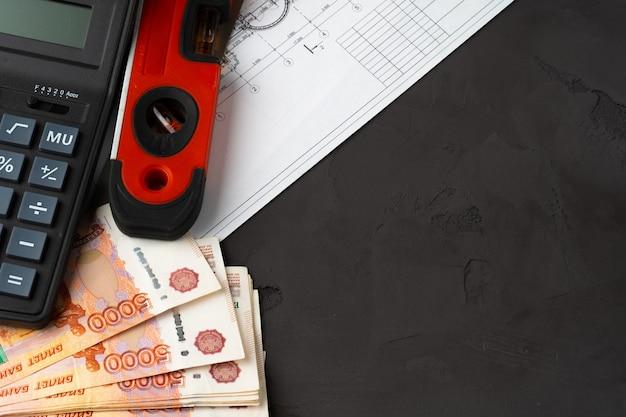 Российские рубли укладываются на чертежи с помощью калькулятора. ремонт, концепция затрат на строительство