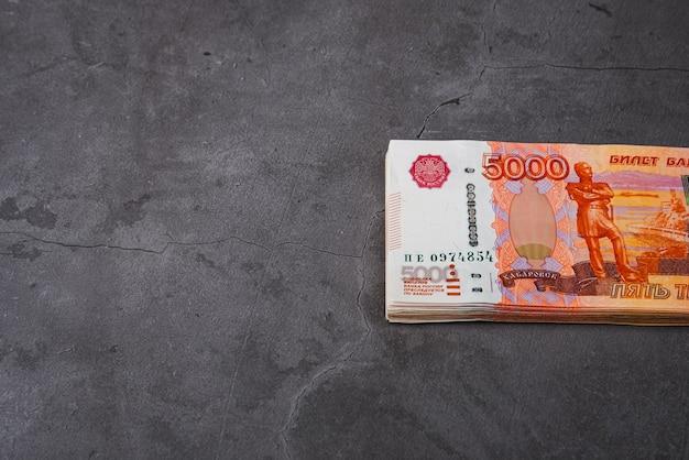 ロシアは灰色の背景に大きな束をルーブルします。 5000ルーブルのノートの束。