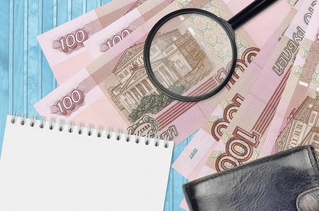Купюры российских рублей и увеличительное стекло с черным кошельком и блокнотом