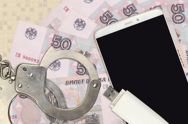 Купюры российских рублей и смартфон с полицейскими наручниками