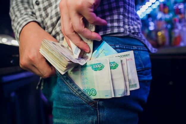 ロシアのルーブル、手、ジーンズ、隠し場所、レジ係の従業員による盗難
