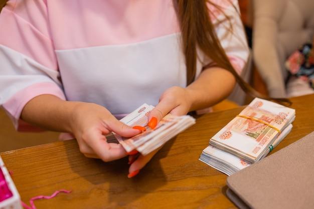 Российские рубли в руке вентилятора. мужская рука, держащая многие российские банкноты. перевод денег. изолированные пятитысячные достоинства российских рублей в руке.