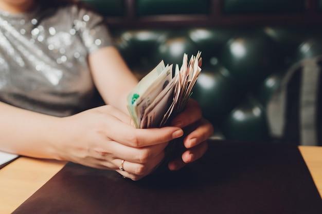 Российские рубли в руке вентилятора. мужская рука, держащая многие российские банкноты. передача денег.