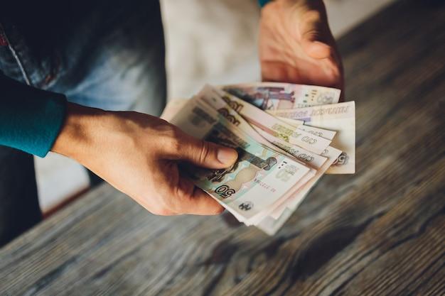 Российские рубли в руке вентилятора. мужская рука держит многие российские банкноты