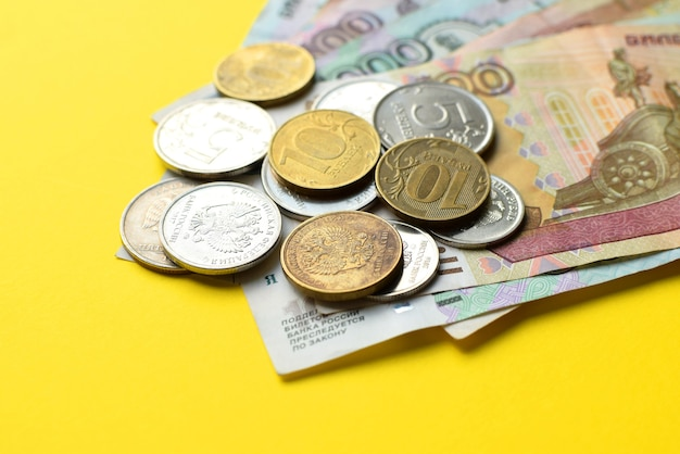 Российские рубли на желтом фоне. банкноты и различные монеты.