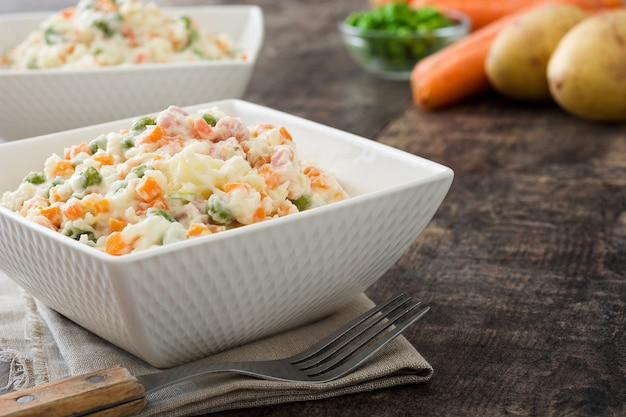 Russian salad and ingredients on rustic wooden