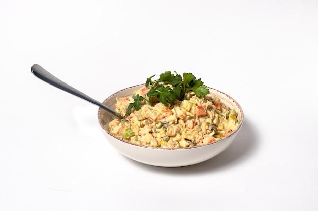 Русский салат оливье из колбасы и овощей на белом фоне.