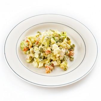 Русский салат оливье на белой тарелке.