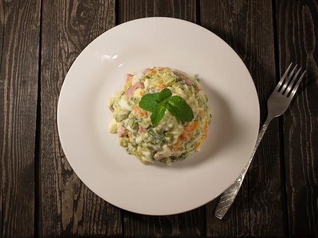 Русский салат оливье с маринованными огурцами и зеленым горошком, отварным картофелем, морковью и яйцом с белым соусом и ветчиной на тарелке на темном деревянном фоне