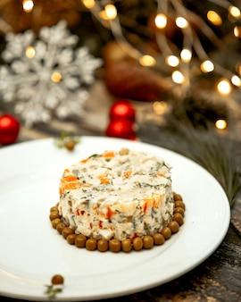 Русский салат подается на тарелке
