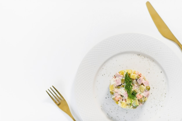Russian salad on a white plate with a golden knife and fork