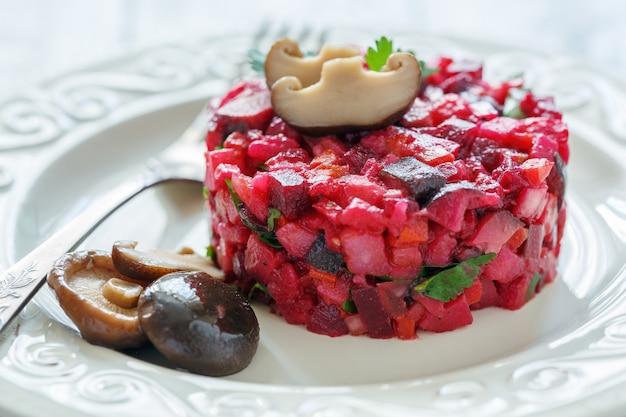 Русский салат с маринованными грибами на белой тарелке